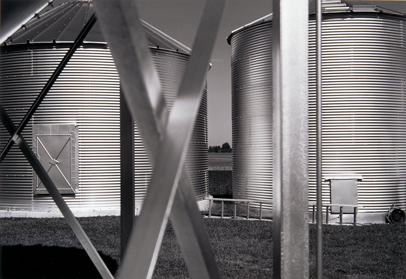 2 short corrugated metal silos with a ladder on the ground in front of them; seen through metal bars creating 2 x's and vertical lines