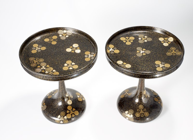round tray with straight, short sides on a tall, round pedestal and wide base; black ground with gold flecks, and gold and mother-of-pearl chrysanthemum design