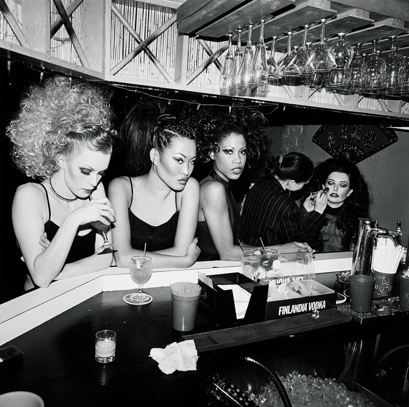 3 women in heavy makeup leaning against a bar; woman at L with curly hair sipping a drink; seated woman at R having makeup applied by a woman in a striped jacket