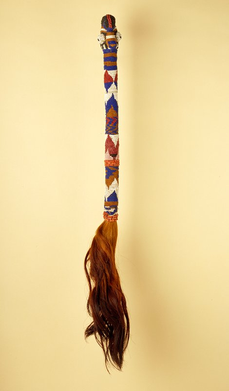 Bead covered handle with geometric zigzag, triangle and striped designs in multicolored beads; head with bulging eyes and mohawk hairstyle at top; long tail of reddish-brown hair at end