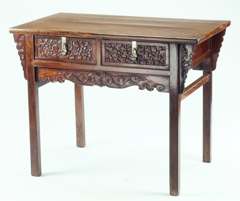 Four-legged table with apron on front and back and leg supports on sides; apron carved on front and back with scrolling organic designs; two drawers on front carved with flowering branches