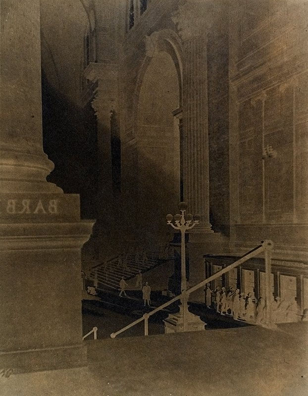 negative print, backwards; view from landing of a short staircase to people at R and people walking on stairs at center; expansive archways and tall columns