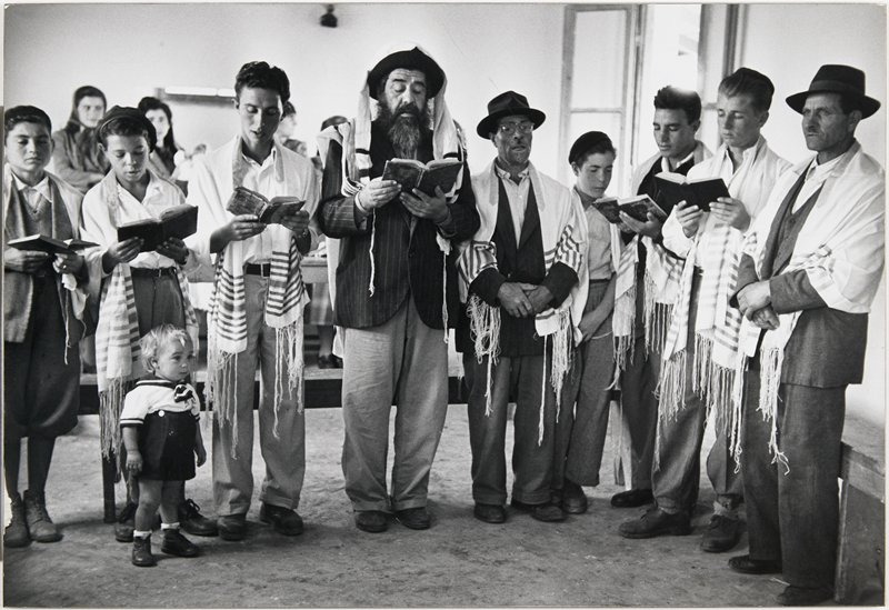 group of people wearing prayer shawls holding open books; small child in front of second woman from proper right; other people in background