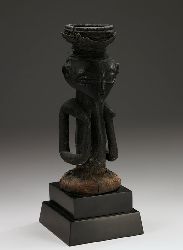 half figure with bent arms free of the narrow torso and hands raised to the pointed breasts; furrowed coiffure topped by a large bowl-shaped receptacle containing vestiges of symbolic ingredients