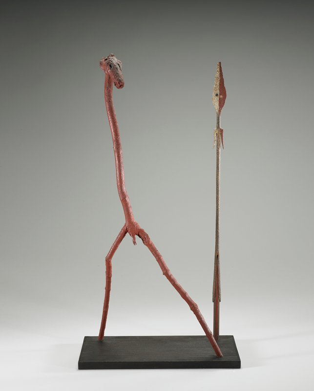 tall, armless, 2-legged male figure with animal's head, at L; vertical spear-like object at R; mounted on a board