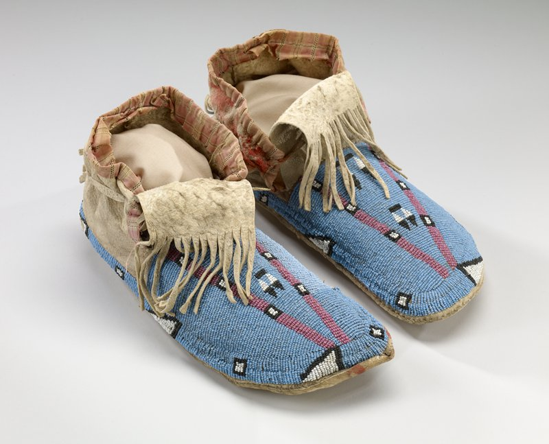 rawhide soles; tanned uppers; beaded geometric designs in pink, black and white on blue ground; fringed tongues; pink plaid cloth around ankles
