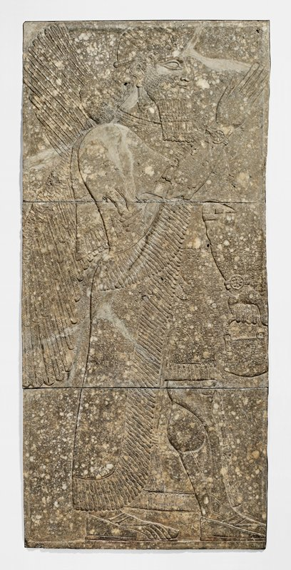 low relief carving of a Winged Genius, from the Northwest palace of Ashur-Nasir-Pal at Nimrud; a wide band of inscribed writing crosses the slab in the central section