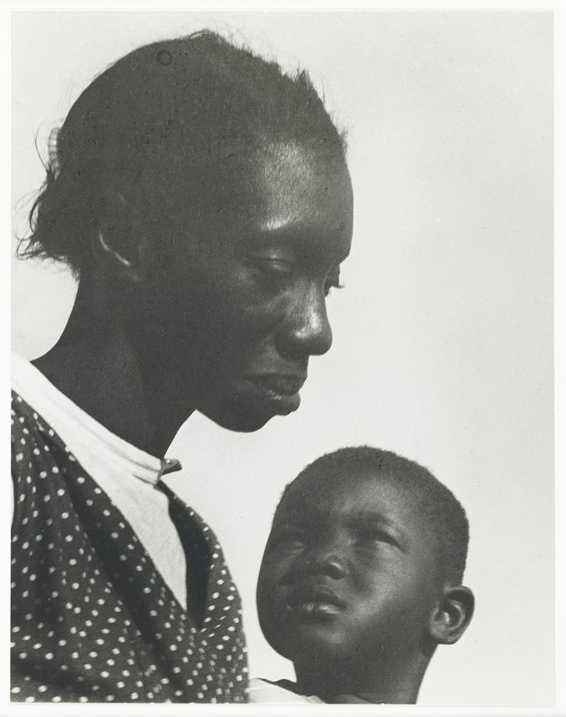 profile of black woman at L; little boy's head at center, bottom, looking up at woman