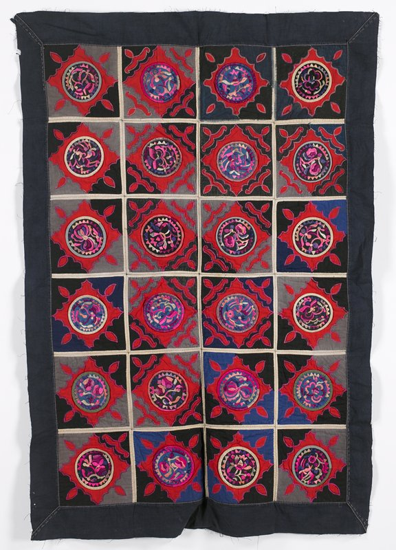 24 squares with appliqué; blue border bands; each square has central embroidered rondel of blue or black; organic red appliqués with grey, black and blue edges