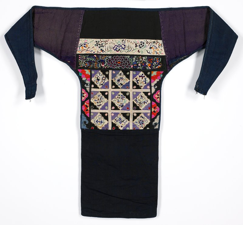 T-shaped; blue backing; dark blue bottom panel; embroidered and appliquéd square main panel with nine square repeating designs; central square flanked with floral appliqué bands in orange, red and pink with greens and blue on black; two top embroidered strips with flowers, figure and bird; purple straps