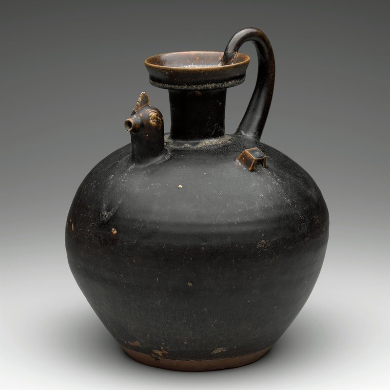 rounded body; short, straight neck with flaring lip; tapering handle; pair of square decorative handles; chicken head spout; black glaze