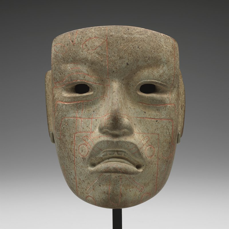 human face with long ears; open mouth with teeth; red linear designs