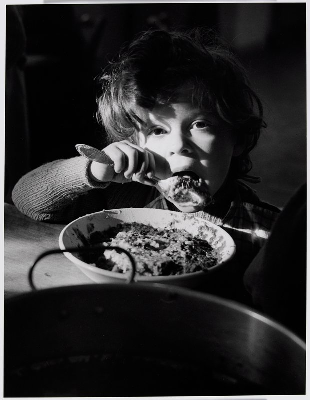 child with curly hair eating from a bowl on a table; child rests PR elbow on table edge
