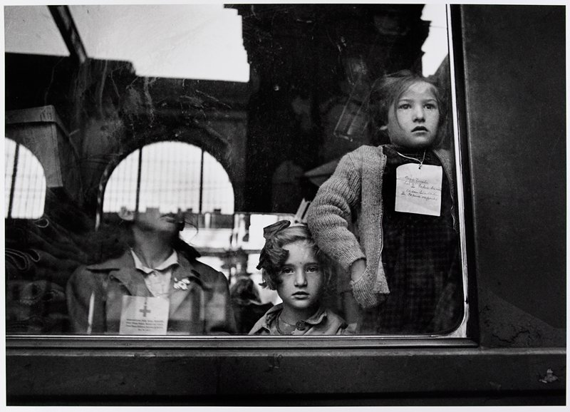 3 figures seen through a window: standing girl at R wearing a sweater and paper tag on a string around her neck, tears in her eyes; head of girl at center with a large bow in her hair; chin, neck and shoulders of a third figure at L visible below reflection