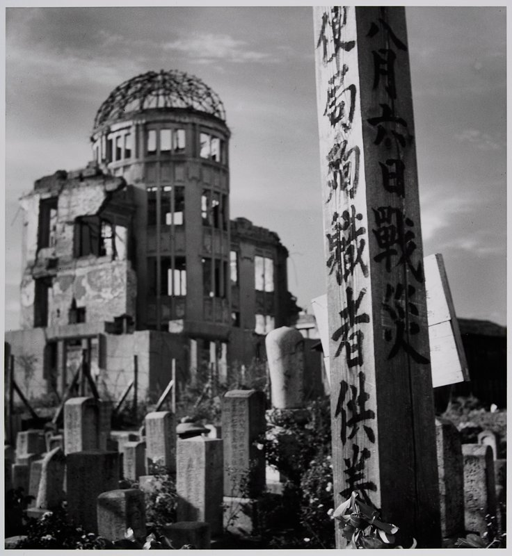 tall wooden post at R with Japanese characters; vertical stone monuments with text in middle ground; ruined building in background at L