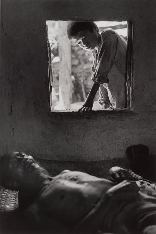 bare-chested old man in foreground lying on a mat; boy with wrinkled brow looking at man through window