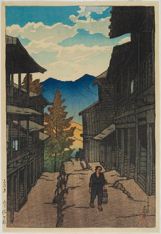landscape; narrow path with figure carrying a bucket; tall buildings at each side of path; mountains in background