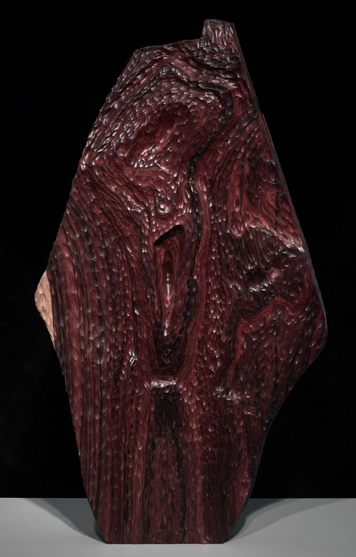roughly diamond-shaped piece of wood; carved on front with small concave scoops; deep scoop near center