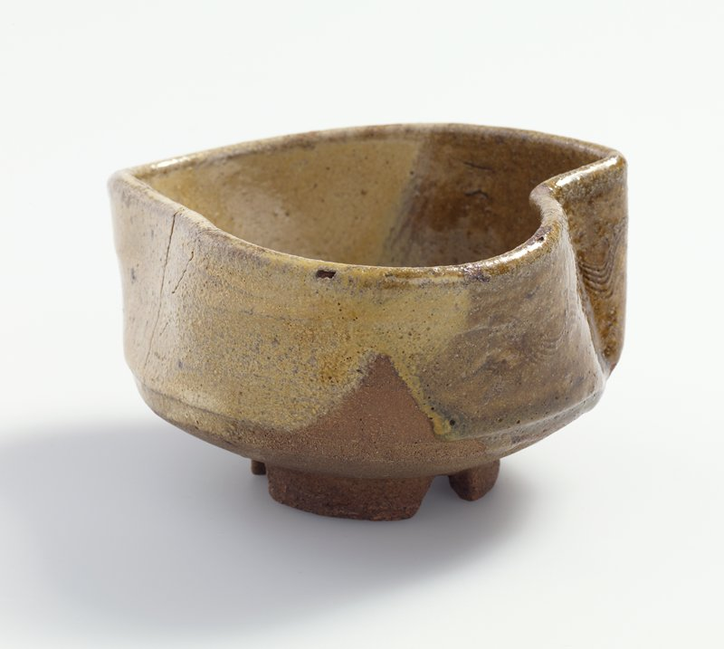 round teabowl pressed into asymmetrical shape; dark brown and tan glazes; light wavy parallel lines on exterior; has storage box