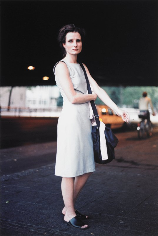 woman with a square face wearing a light blue sleeveless dress and black slides, with a black bag over her PL shoulder and a cigarette in her PL hand