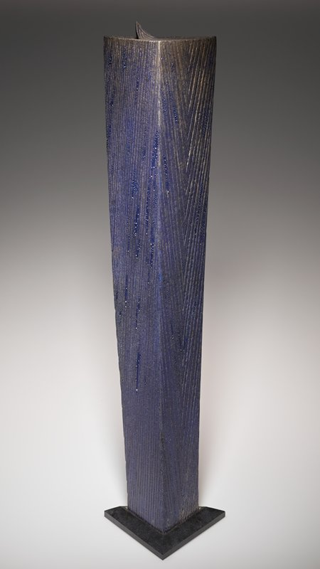 triangular form with flat top and bottom; tapering to smaller base; incised vertical lines; silver over blue forming moist-looking droplets; lifting corner at top; separate grey granite base included