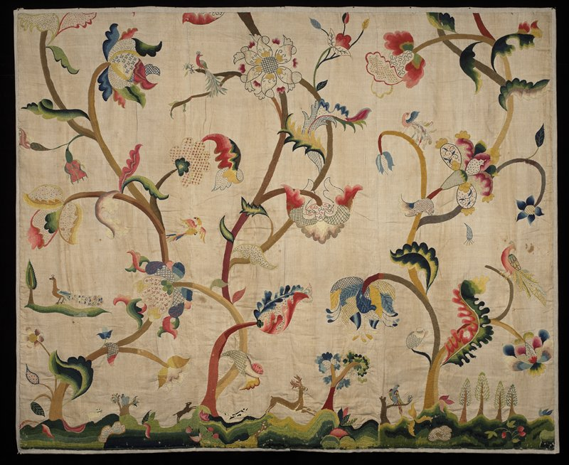 multicolored embroidery depicting overall scene of fanciful birds perched on curvaceous flowering trees; very bottom depicts rolling hills with a deer in the center and other small animals prancing about the ground; double layer backing; light brown background