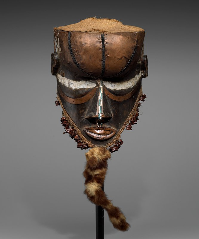 helmet mask; triangular face with small eyes; large nose; bead lines on forehead and down nose; animal fur beard with nut shells at sides; cloth at top and back with blue and white beading on back