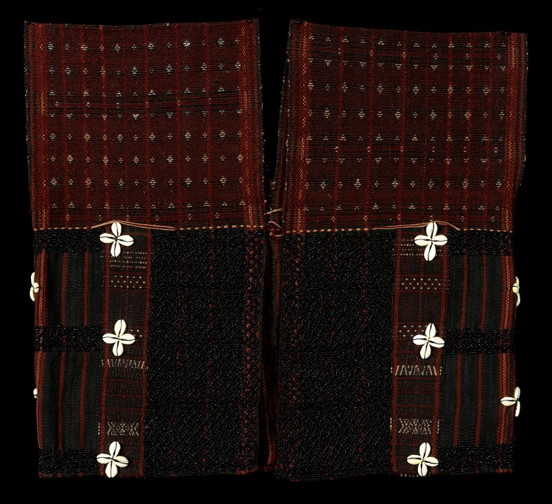 Red and black pattered ground with light brown supplementary weft patterning; panels of beadig in a net-like pattern on front and back, small sections of beaded pattern at sides, below arm holes.