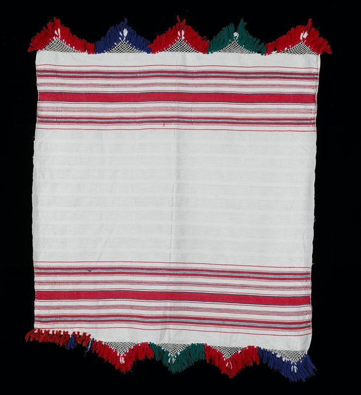 White background with red and blue weft stripes on both ends, macrame work at ends, with fringe in red, green, blue.