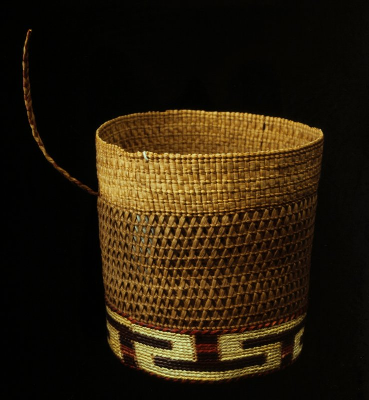 Round basket in a bandbox shape with cover. The technique is a combination of plain twined weaving (near base), crossed-warp twined (in center), and an alternating checker and twined (at rim). There are bands of false embroidery at the bottom, on the cover, and the rim of the cover. Materials are a foundation of spruce root, with false embroidery of grasses. Design consists of two bands of reversed T-bars in red and purple, and a spiral on the cover in white and two shades of red.