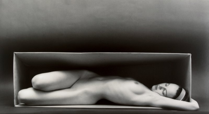nude woman lying in a horizontal box; knees folded back and arms overhead