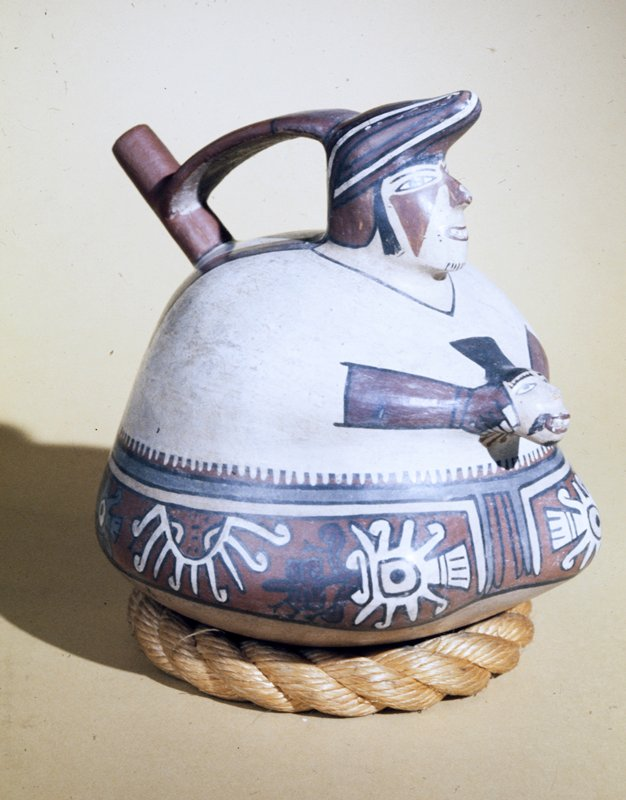 Bottle in form of a Woman's figure holding a human head . Upper body of polished cream slip. Lower area of dark red with a band of stylized human heads painted in polychrome. Nose, teeth arms, and accessory head modelled, other details painted. The spout, emerging from back of shoulders, is a bridged to top of head by a narrow band which forms the handle of jug. Rounded bottom, stand.