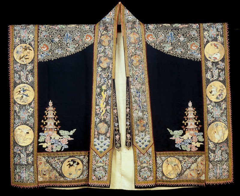 Taoist priest robe of embroidered black satin. All-over tendril background of couched gold threads. Conventional Taoist motives, Buddhist symbols, bats, clouds, etc., in couched gold medallions * are figures of the Eight Immortals, chilin, bear, and various birds in colored satin stitch. On front border are phoenix medallions, white tiger, etc. All borders edged with Greek key meander in couched yellow twist. Lining of yellow satin of dragon medallion design. A magnificent example. *late additions