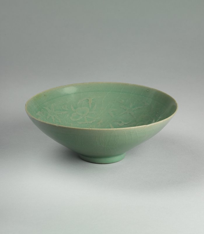 celadon colored bowl with floral motif embedded under glaze; small foot, wide mouth