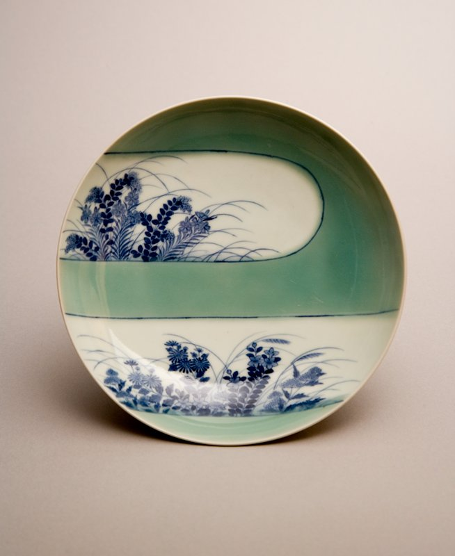 shallow dish with stylized design of green fog revealing blue flowers, ferns, and grasses; blue floral and vine designs on underside; blue vertical bars painted on foot