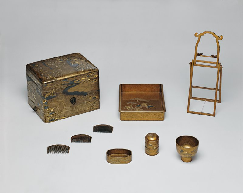 toiletry set with box, three combs of varying fineness of teeth; small chalice with pine and floral design; and other small containers, all flecked gold with pine tree and floral designs; mirror stand; box decorated with pine trees, carriages, boats, and silver clouds; tray decorated with pine tree