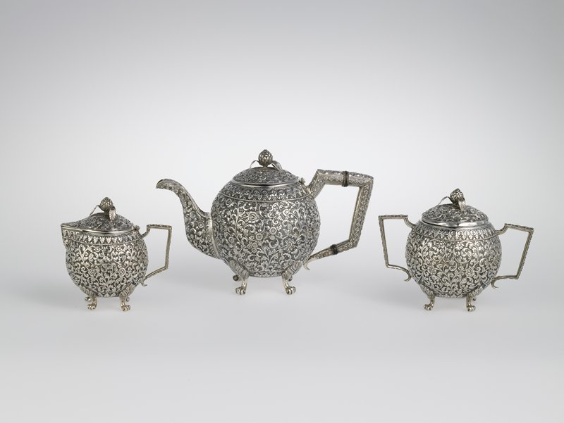 spherical body; hinged lid with organic finial with three raised leaves; four scrolling feet; overall decorations (body, cover and handle) of relief floral designs