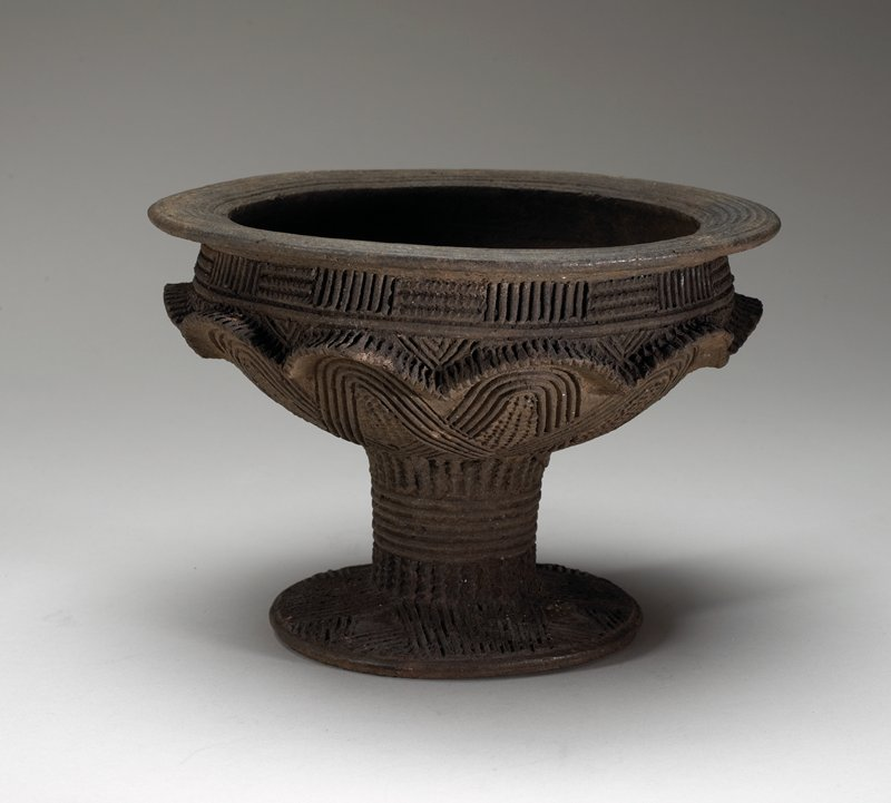bowl-shaped vessel with footed stem base; decorated on exterior and rim with incised geometric designs and raised scallops below rim; dark patina
