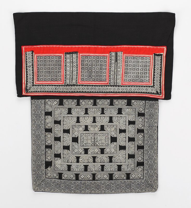 square panel with white geometric cross-stitch design on black of concentric rectangles; woven black and white patterned border; rectangular section of red, white and black applique on black and white geometric and flori-form embroidered designs