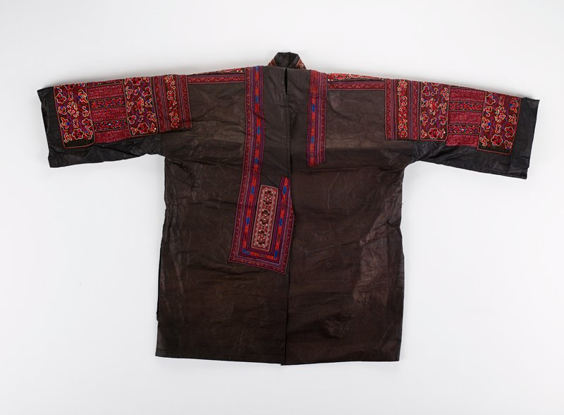 coated, paper-like purple cloth, lined in dark blue; sleeves, shoulders, front opening and collar decorated with embroidered bands including flowers, geometric designs, birds, dragons, fish and fanciful animals in bright red, blue, purple, white and yellow; band at front and band at neck of geometric applique