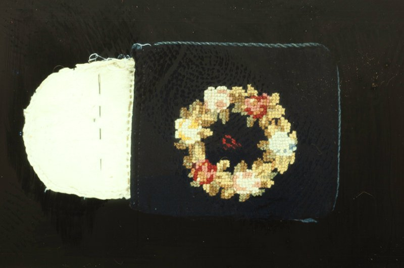 Small pocket book or sewing kit of black woolen material decorated with floral wreath, worked in cross stitch, on both sides. Inside are three flaps of white flannel to hold needles.