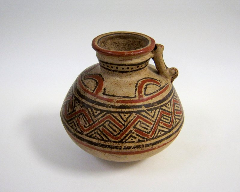 Water jar with a bulbous body and short neck. Around the body a band of geometric design in red and black known as the alligator pattern. From the top of the band project four hook motifs in red bordered with black. Small handle of dissolved animal shape. Body badly cracked