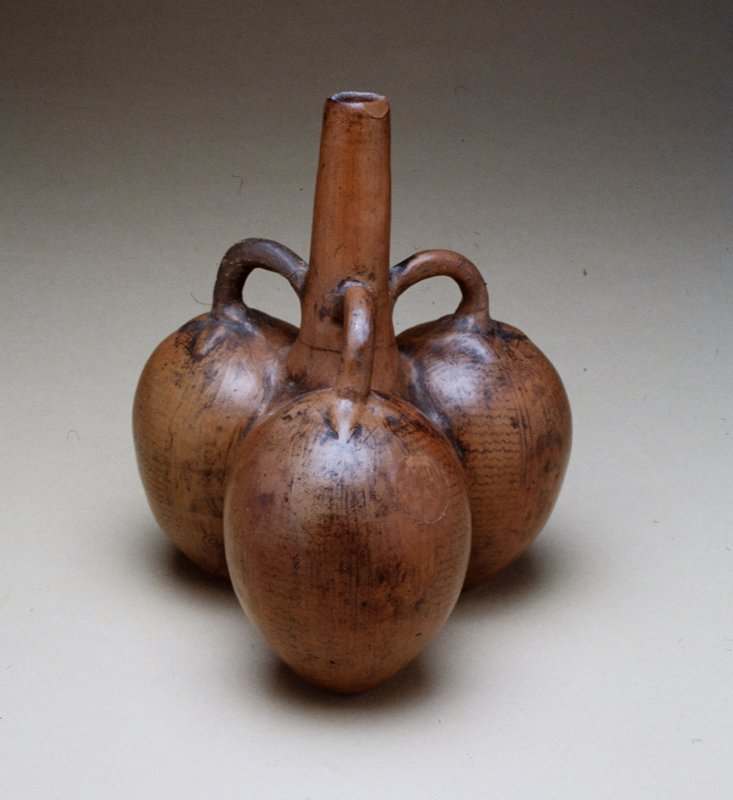 Jar modeled in three sections, representing fruits, with three loop handles attached to base of spout. Burnished surface decorated with vertical panels of stylized birds alternating with panels of horizontal zigzag lines in black on a brown ground.