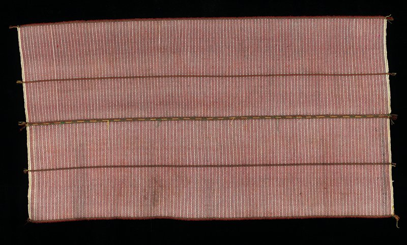 Two panels stitched together. Ecru background with red, pink, black patterning in stripes and diamonds. Six small tassels at each end.