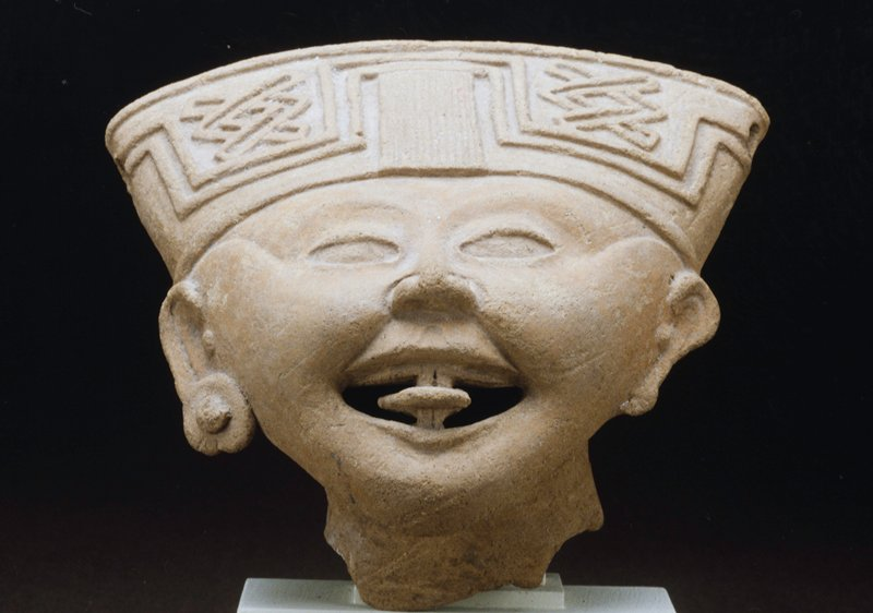 Smiling Face, ceramic, fragment of a larger figure, H. 5 in., W.7 in. Hollow head with open mouth and protruding tongue. Headdress with may symbols, ears with earplugs (one missing). Chips in headdress and two holes in back of head. Nopiloa. The object numbered 47.2.40 does not match the photograph on the Catalog card, although it is an extremely similar piece. See second Catalog card with same number 47.2.40. for other object. Wide face with sloping forehead, almond shaped eyes, and lips parted in an infectious smile. Small earplugs and turban-like headdress of which the central portion is broken away. Unglazed greyish clay.-original object-cat. card