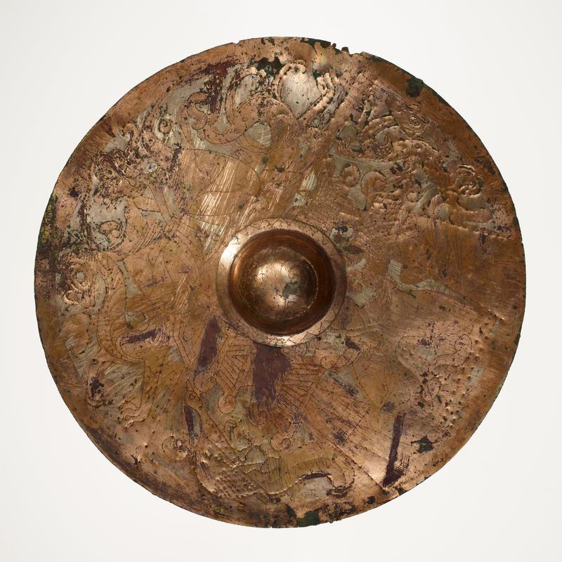 flat, round disc with domed protrusion at center; incised with figures, birds, animals and designs; mounted on black cloth-covered board with L2003.116.2.1