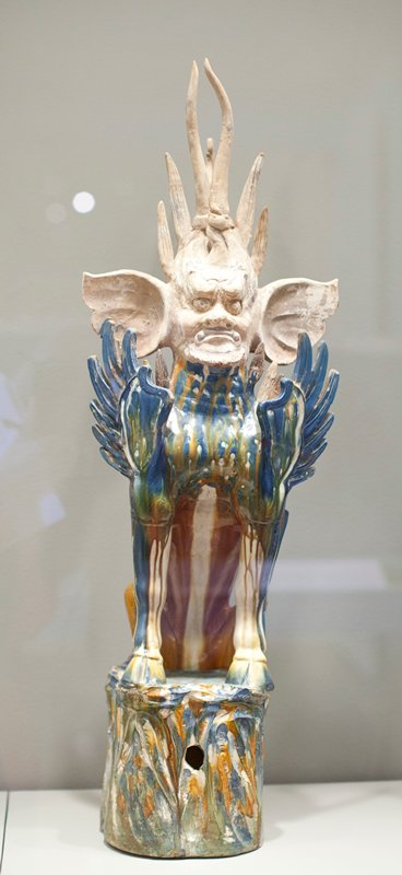 Earth Spirit with human head and removable flame halo. ca. 725 A.D. Glazed pottery tomb figure, one of a pair, on a deep cylindrical base with mottled glaze. The figure is predominantly blue, with white areas. Head and halo unglazed.