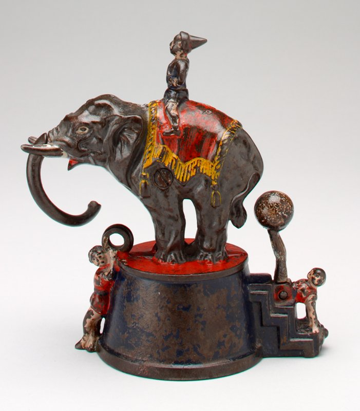 elephant on pedestal; one clown sitting on elephant; one clown below elephants trunk holding two rings; one clown at base of pedestal below elephant's tail balancing a ball on his feet