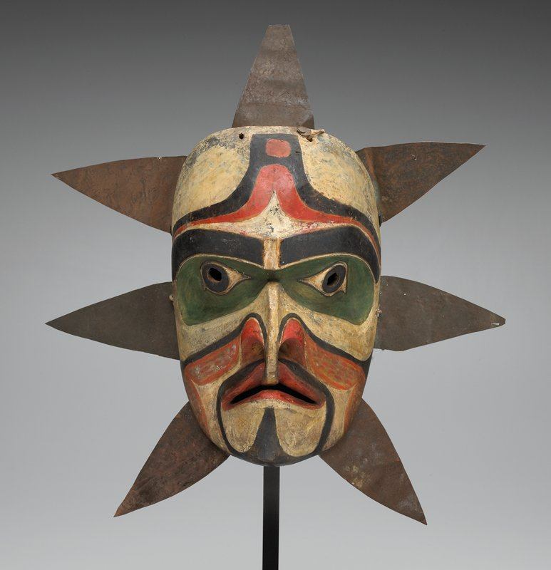 mask with seven radiating triangular pieces of metal; large eyes, rimmed in green; flat bridge of nose extends downward into mouth; orange, black and white marks on face