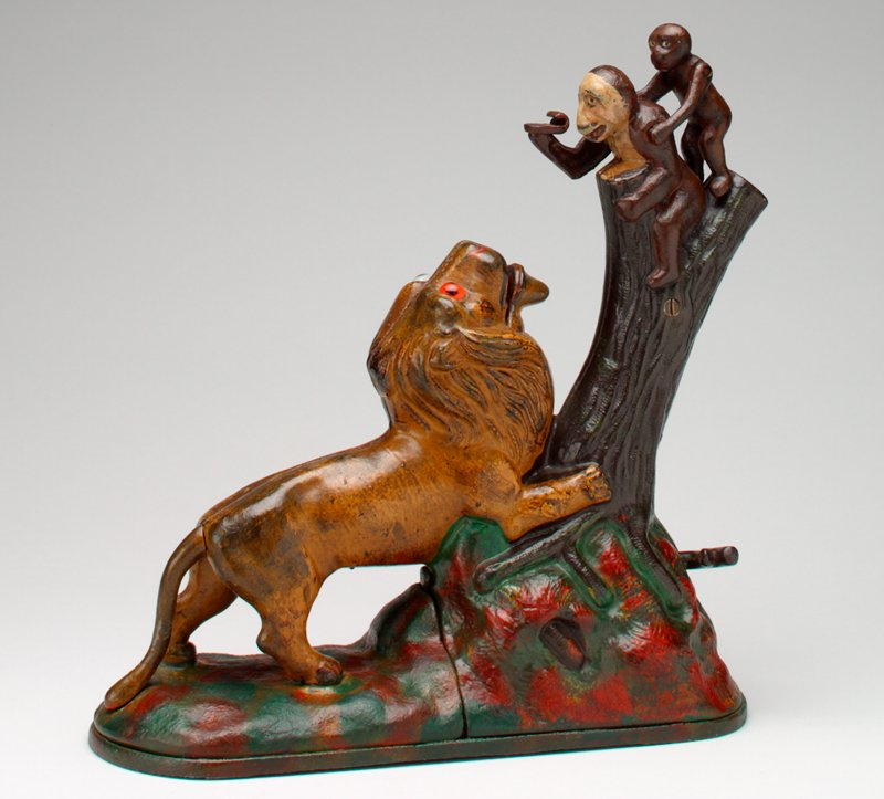 lion at base of tree trunk and two monkeys on top of tree; all stand on oval-like green and red platform